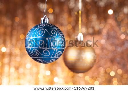 Blue and gold christmas baubles on background of defocused golden lights.
