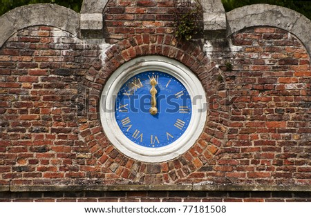 blue and gold outdoor clock set in an ornate decorative brick wall