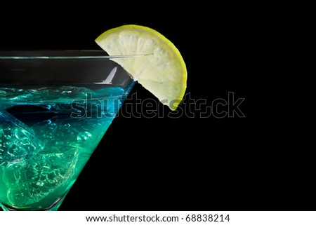 Blue and green cocktail in martini glass with lemon on the rim isolated on black background