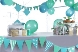 Blue and green colored birthday party table with sweets and decorations