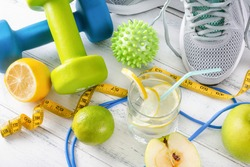 blue and green dumbbells, a glass of water with lemon, gray sneakers, a ball, measuring tape on a white background