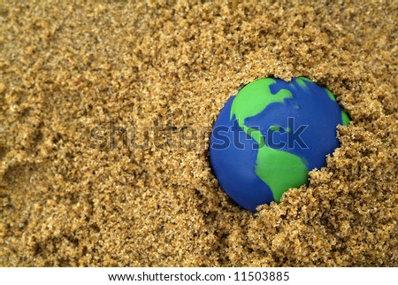 blue and green globe buried in sand