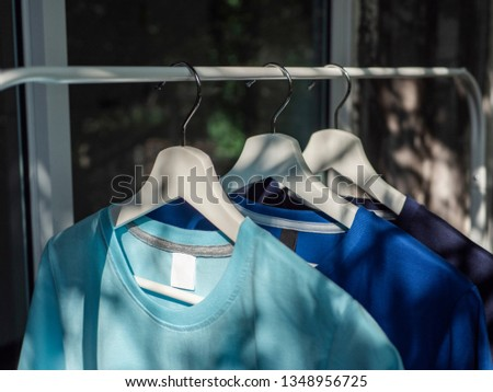 Blue and navy blue t-shirts on hangers, close up view  #1348956725