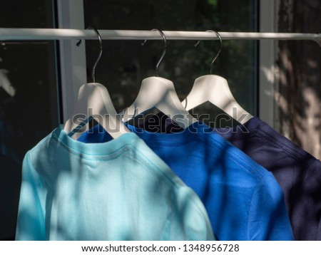 Blue and navy blue t-shirts on hangers, close up view  #1348956728