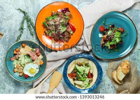 Blue and one special plate with different salads: tuna salad, beef salad, squid salad, warm salad with grilled vegetables. Beautiful serving of dishes. Light gray background. Restaurant menu