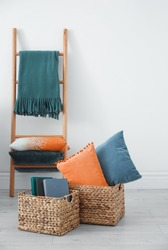 Blue and orange pillows in wicker basket near decorative ladder indoors