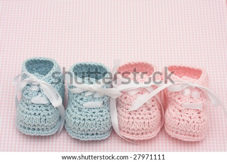 Blue and pink baby booties on a pink background, baby booties