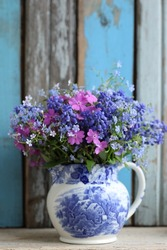 Blue and pink bouquet, bunch flowers in vintage china creamer, pitcher on wooden aged, weathered wooden background, vertical photo, daylight
