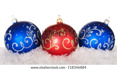 blue and red christmas balls with pattern on snow on white background