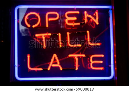 Blue and red neon sign of the words 'Open till late' inside a square of neon, on a black background.