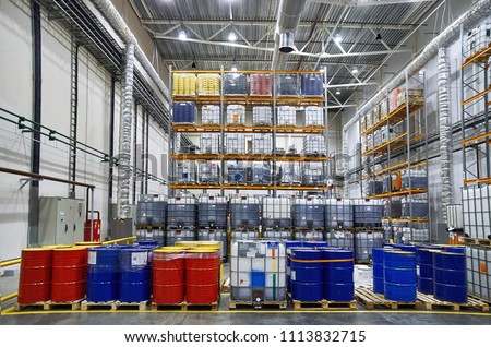 Blue and red oil drums and plastic container on pallets in a warehouse on metal shelving. Handling and storing industrial lubricants. Hazardous Material Storage