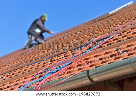 Blue and red photovoltaic cables on the roof with worker in the background. Soft front focus with shallow depth of field