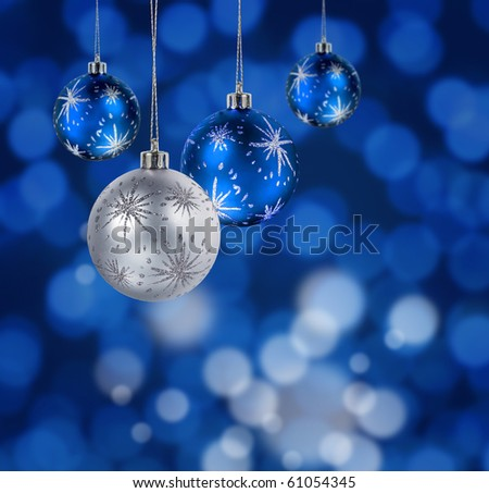 Blue and silver Christmas balls hanging against blue light spots background