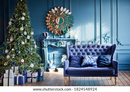 Blue and silver Christmas interior. Living room with blue walls, blue sofa and silver and blue Christmas decorations on Christmas tree