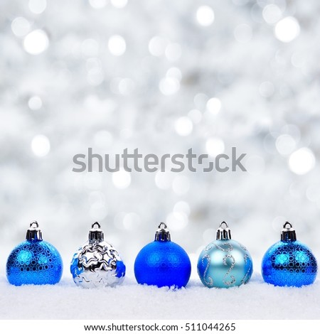Blue And Silver Christmas Ornaments In Snow With Twinkling Background 511044265