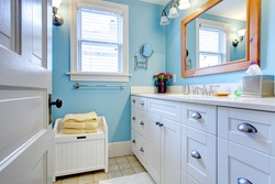 Blue and white bathroom with lots of storage space with open door.