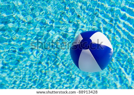 Blue and white beach ball in clear water of swimming pool
