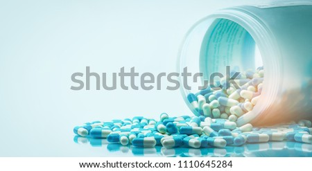 Blue and white capsules pill spilled out from white plastic bottle container. Global healthcare concept. Antibiotics drug resistance. Antimicrobial capsule pills. Pharmaceutical industry. Pharmacy.