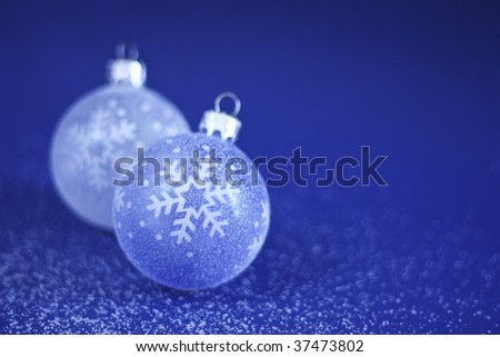 Blue and white Christmas Baubles on blue background with sprinkles of snow.
