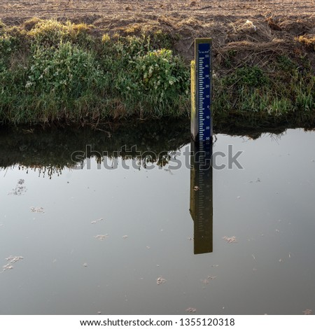 Blue and white colored water level meter in a Dutch ditch reflected in the mirror smooth water surface. The meter indicates the water level in relation to the Normal Amsterdam Level (NAP). Stok fotoğraf ©