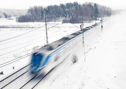 Blue and white commuter train in blurred motion in snowstorm