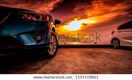 Blue and white compact SUV car with sport and modern design parked on concrete road by the sea near the beach at sunset. Environmentally friendly technology. Road trip on vacation travel.