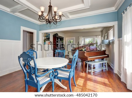 Photo of Blue and white dining area with nice table set. Piano at the background. Northwest, USA