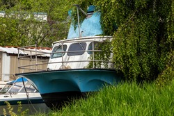 Blue and White Fishing Boat Sitting in a Yard Aged by the Weather and Surrounded by Overgrown Foliage