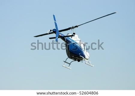 Blue and white helicopter in midair flight.