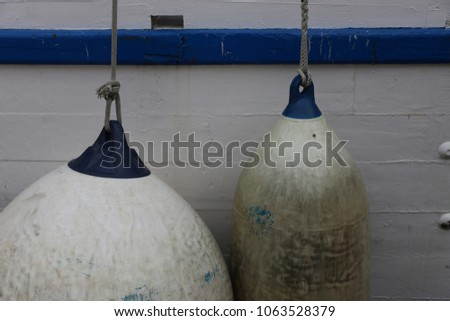 Blue and white plastic floaters hanging from the deck of a wooden boat. Close up view of part of a painted ship. Geometric elements of different shapes, round and oval. Maritime equipment with ropes. #1063528379