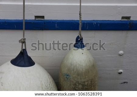 Blue and white plastic floaters hanging from the deck of a wooden boat. Close up view of part of a painted ship. Geometric elements of different shapes, round and oval. Maritime equipment with ropes. #1063528391