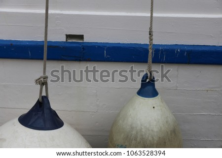 Blue and white plastic floaters hanging from the deck of a wooden boat. Close up view of part of a painted ship. Geometric elements of different shapes, round and oval. Maritime equipment with ropes.