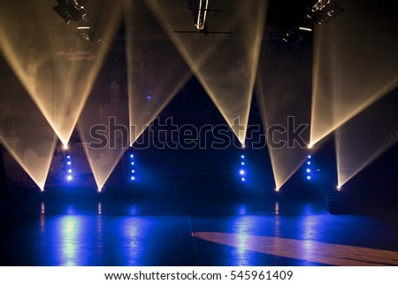 Blue and white spotlights on a stage #545961409