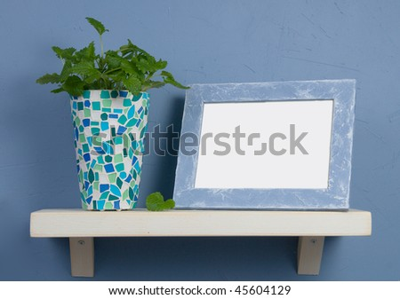 Blue and white still-life with mosaic vase and frame - stock photo