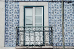 Blue and white tiled window with iron balcony in Lisbon Portugal