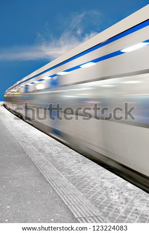 Blue and white train passing station at high speed