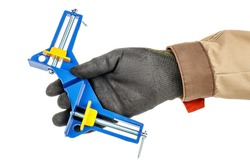 Blue and yellow angle clamp in worker hand in black protective glove and brown uniform isolated on white background