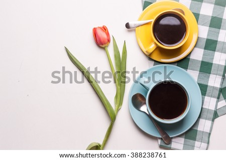 Blue and yellow cups of coffee with red tulip on white background #388238761