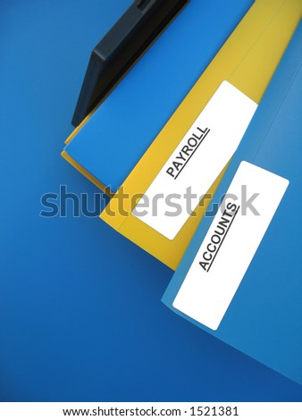 "Blue and yellow folders sitting on an office tray. One folder is labeled ""PAYROLL�. Another folder is labeled ""ACCOUNTS�."