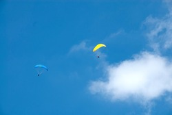 Blue and Yellow Hang Gliders Soaring Through the Air