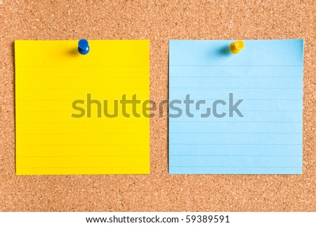 blue and yellow stripped notes attached by yellow and blue pins on cork board