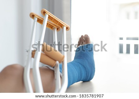 Blue ankle and foot splint Bandages on the legs from a young man's fall accident, Blue plaster on the ankle, Crutches assist in the walking of the patient. Stock photo ©