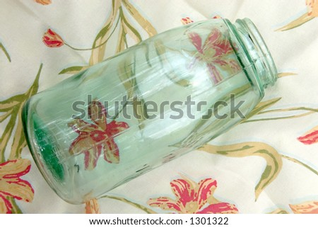 Blue antique glass jar used for canning fruits and vegetables,  sitting on a vintage table cloth.