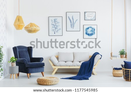 Blue armchair next to a grey sofa, wicker pouf and lamps in a living room interior. Real photo #1177545985