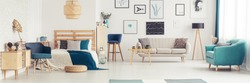 Blue armchair next to bed and wooden cupboard in bedroom interior with couch and gallery