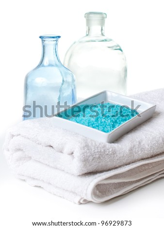 Blue aromatic salt, white towels and a bottles