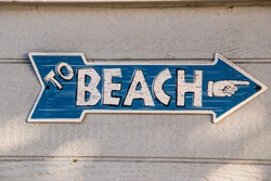 Blue arrow shaped sign with white letters saying to beach with a hand icon pointing in the arrow's direction