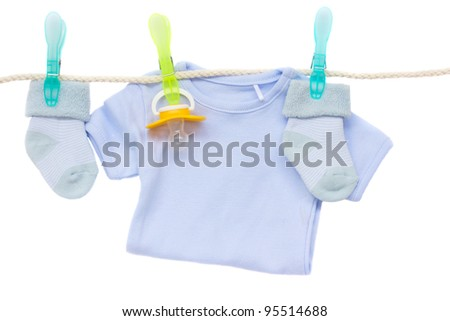 blue baby clothes and soother hanging on rope isolated on white