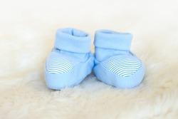Blue baby newborn booties on white background