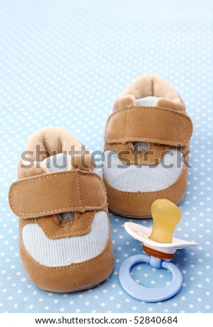 Blue baby shoes and dummy on spotted background